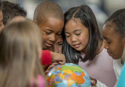 Several young kids gathered around a small globe, pointing at various spots.