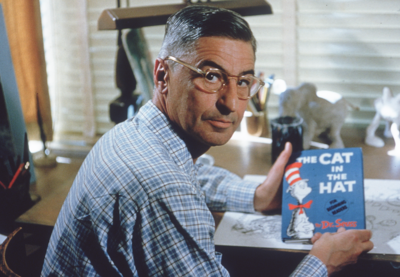 Theodore Seuss Geisel, also known as Dr. Seuss, holding a copy of his book 'The Cat in the Hat'