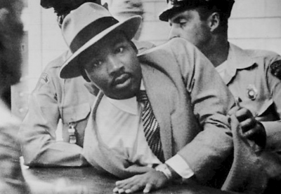 Dr. Martin Luther King, Jr. being detained and arrested by uniformed police officers.
