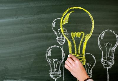 Lightbulbs drawn in yellow and white chalk on a chalkboard.