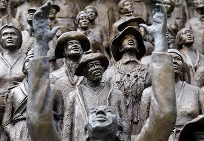 Statues depicting emancipated enslaved people celebrating and looking towards the sky.