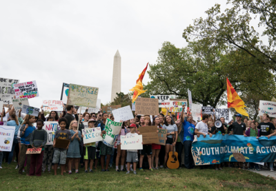 A group of young people holding signs in front of the Washington Monument for the Youth Climate Action Global Climate Strike.
