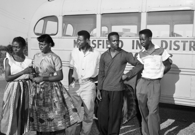 Black students in Mansfield, TX during integration crisis, standing in front of a school bus