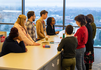 Teaching Tolerance staff members gathered together around a counter discussing something. A view of downtown Montgomery, Alabama is visible in the background.