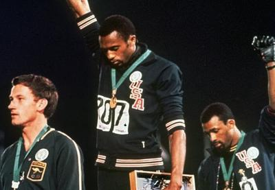Tommie Smith and John Carlos raise their fists at a 1968 Olympic medal ceremony.
