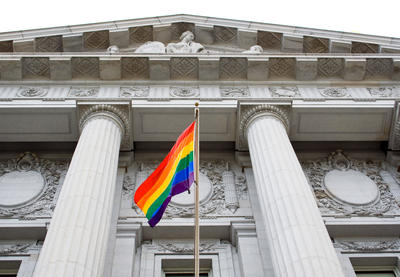 LGBTQ pride flag flying in front of courthouse-like building.