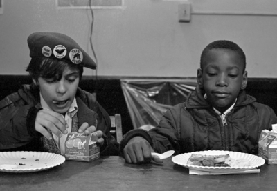 Two kids eating breakfast together.