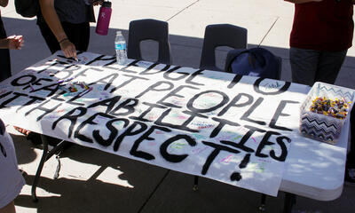 handmade sign reads I pledge to treat people of all abilities with respect