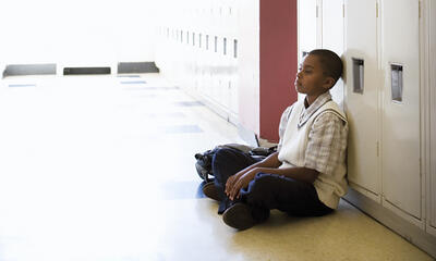 Young African-American Child Sitting Against Locker