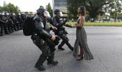 A female BlackLivesMatter protester in a long dress looks straight ahead as two police officers in riot gear approach her.