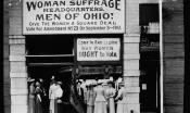 "Black and white photo of suffragists in front of their office with signs that read, ""Come in and learn why women OUGHT to vote"" and ""Woman suffrage headquarters. Men of Ohio! Give the women a square deal. Vote for amendment No. 23 on September 3, 1912."""