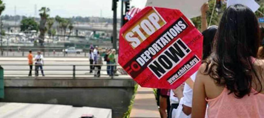 "AFT link photo of protestor holding sign that says ""Stop deportations now!"""