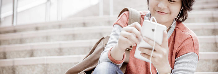 student on steps looking at cell phone smiling