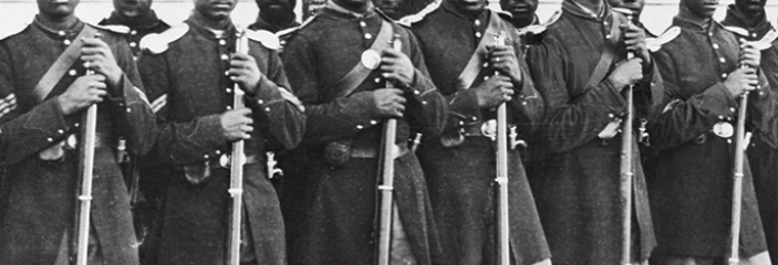 Black Union soldiers standing outside in a line in uniform looking at the camera