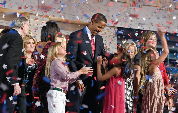 Barak Obama surrounded by children under a confetti rain