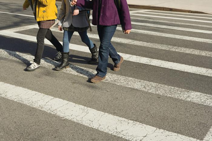 3 Students crossing the road together