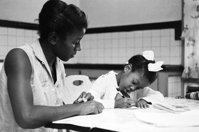 A black teacher instructs a young black student