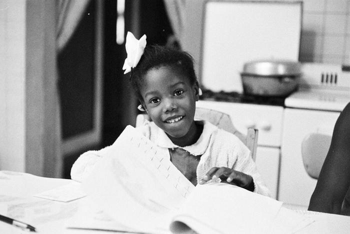 Ruby Bridges smiling as she does her homework