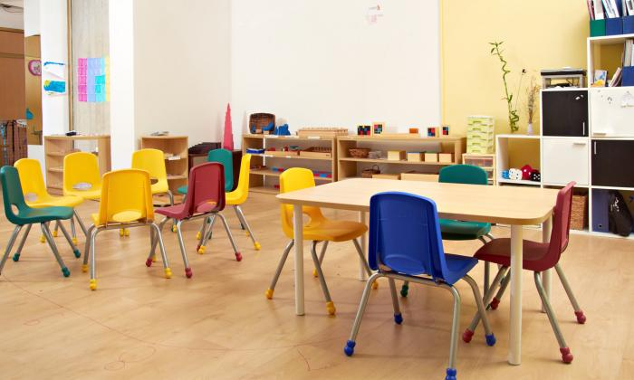 empty rainbow chairs and tables in classroom