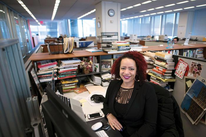 Nikole Hannah Jones sitting at her desk, covered in books and notes
