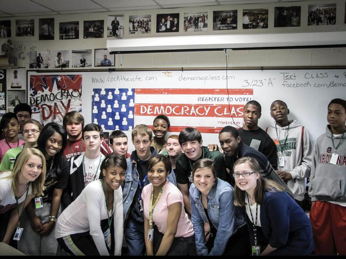 Students participating in Rock the Vote pose in front of American flag