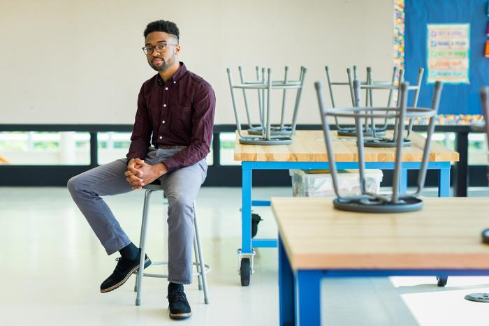 Educator Patrick Harris sitting on a stool in a classroom