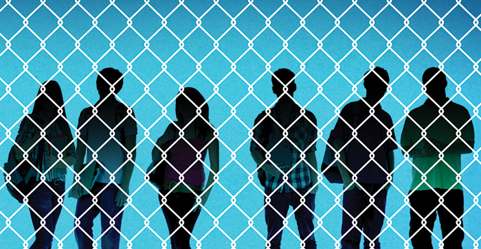 Student silhouettes behind a chainlink fence.
