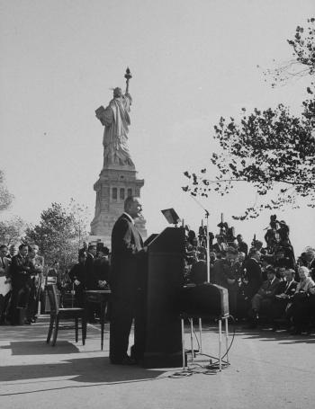 President Lyndon B. Johnson signing immigration reform under Statue of Liberty