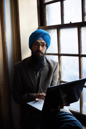 Vishavjit Singh sits at a window with his computer.