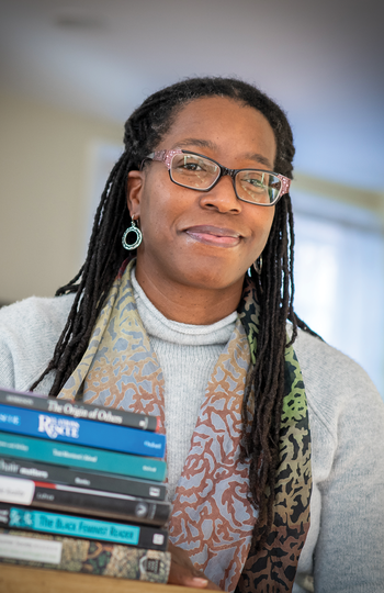 Professor Tiya Miles sitting behind a stack of several books.