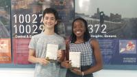 Two students holding copies of the book 'Evicted: Poverty and Profit in the American City.'